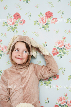 Portrait of young girl (5,6) in bunny costume touching ear, wallpaper