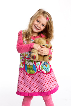 Portrait of happy litlle girl with her teddy,bear wearing colourful dress in front of