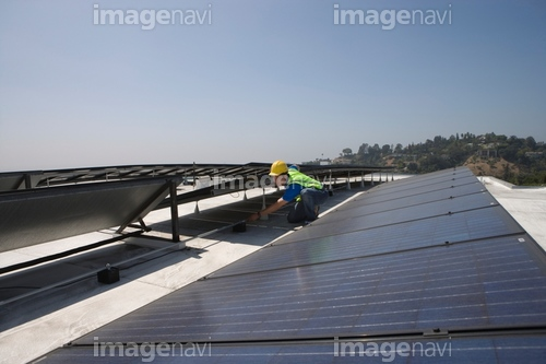 Maintenance worker checks solar array on rooftop in Los Angeles, California