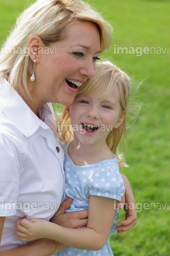 緑の中で抱き合う女の子とお母さん