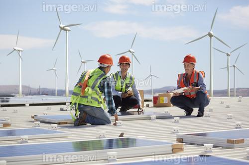 Engineers installing solar panels at alternative energy power plant