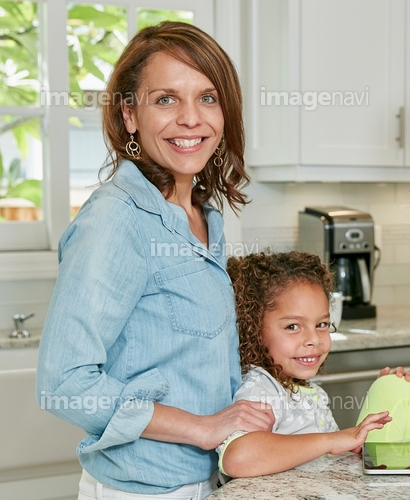 Side view of mother behind daughter in kitchen looking at camera smiling