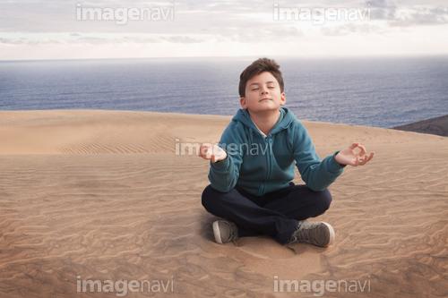 Hispanic boy meditating on sand dune over ocean