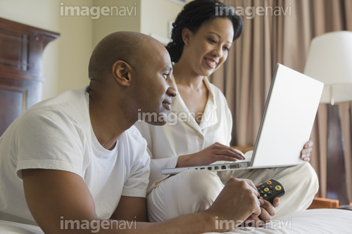 African couple in bed using laptop