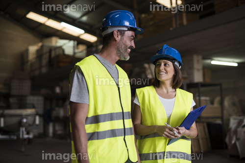 Two construction workers talking in warehouse of construction company