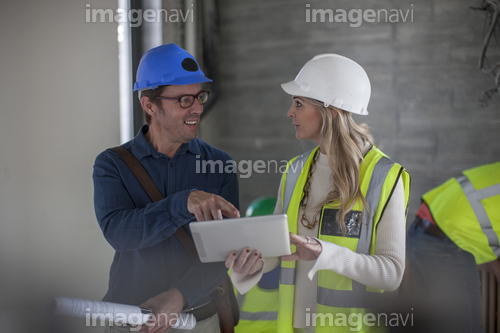 Man and woman on construction site with hard hats and tablet