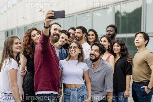 Man taking selfie with group of friends in city
