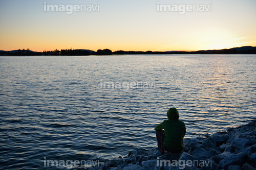 Sweden, Storuman, Man by the lakeside at sunset