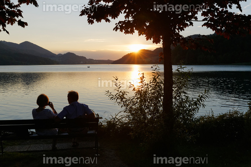 Austria, Salzburg State, Fuschlsee Lake, Fuschl am See, Couple on bench at sunset